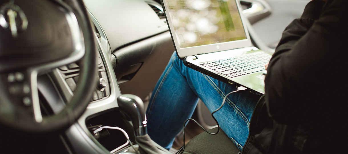 Außendienstmitarbeiter mit Laptop im Auto - Rechtsanwalt Schleifer berät speziell Arbeitnehmer im Außendienst